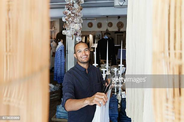 Smiling male owner holding coathanger while standing at fashion store