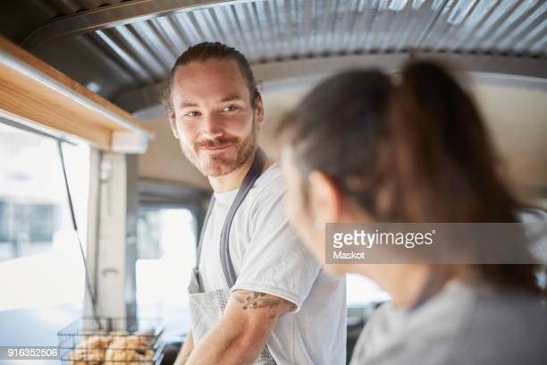 Smiling male owner looking at female colleague in food truck