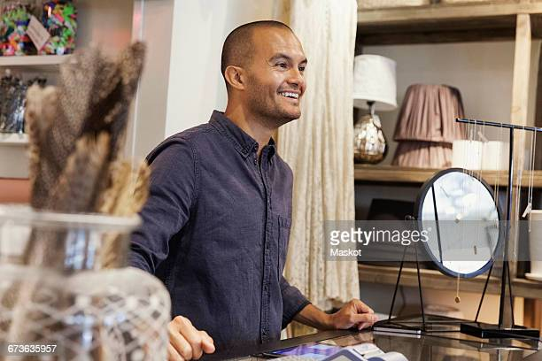 Smiling male owner looking away while standing at store