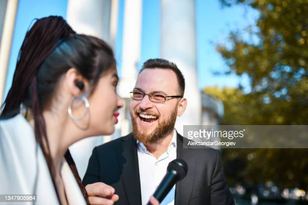 smiling male politician cracking a joke during interview with female journalist - presidential candidate stock pictures, royalty-free photos & images