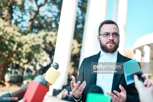smiling male politician explaining society progress during press conference - presidential candidate stock pictures, royalty-free photos & images
