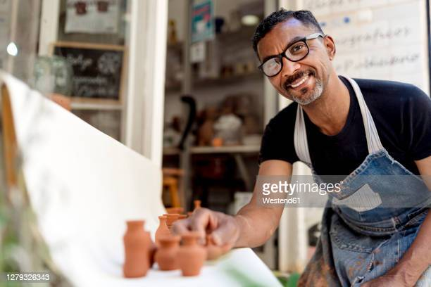 smiling male potter with miniatures on table working in workshop - 1 minute 50 ストックフォトと画像