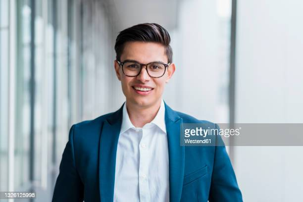 smiling male professional in businesswear standing at corridor - focus on foreground stock pictures, royalty-free photos & images