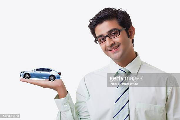 Smiling male sales executive holding car model over white background