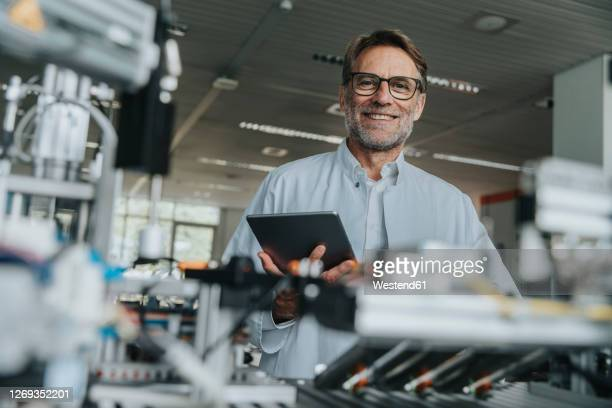 smiling male scientist holding digital tablet while standing by machinery in laboratory - ingenieur stock-fotos und bilder