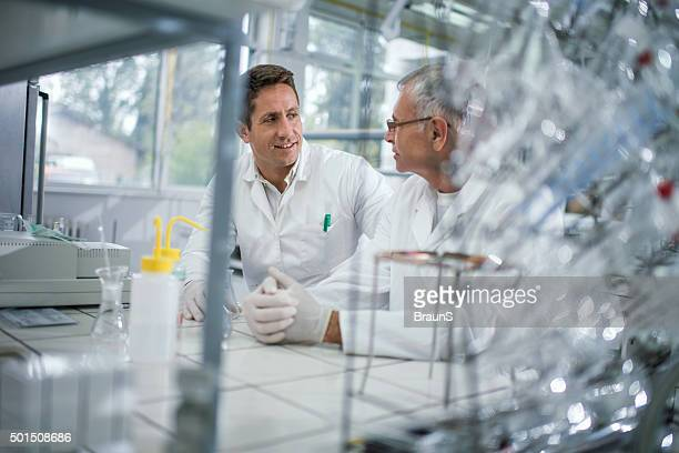 Smiling male scientists talking to each other in laboratory.