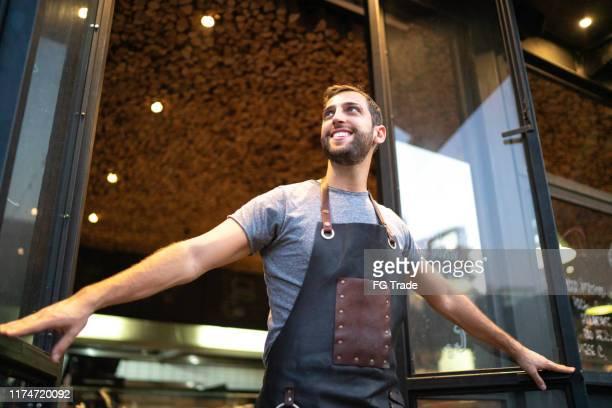 smiling male shop owner looking away in doorway - descoberta imagens e fotografias de stock