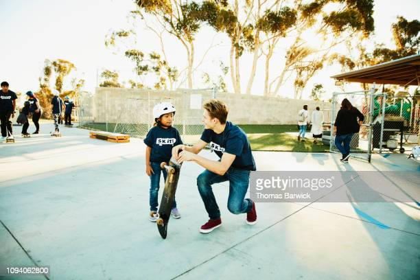 smiling male skateboard instructor in discussion with young student during skate camp - skateboardpark stockfoto's en -beelden