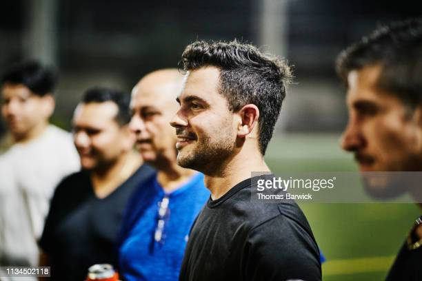 smiling male soccer player hanging out with friends after nighttime soccer game - cinq personnes photos et images de collection