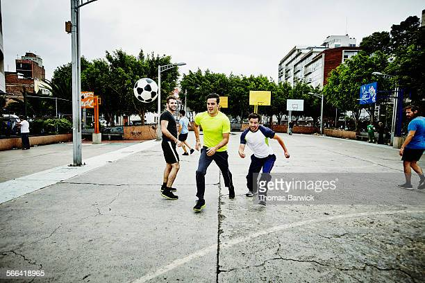 Smiling male soccer players racing for soccer ball