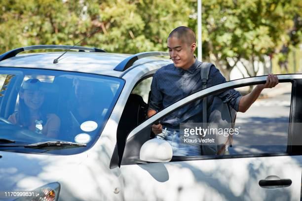 smiling male student entering car on roadside - 入る ストックフォトと画像