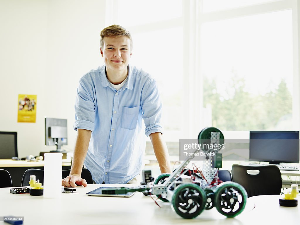 Smiling male student in classroom with robot : Stock Photo