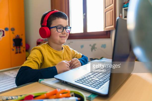 smiling male student listening through headphones while looking at laptop during homeschooling - ホームスクーリング ストックフォトと画像