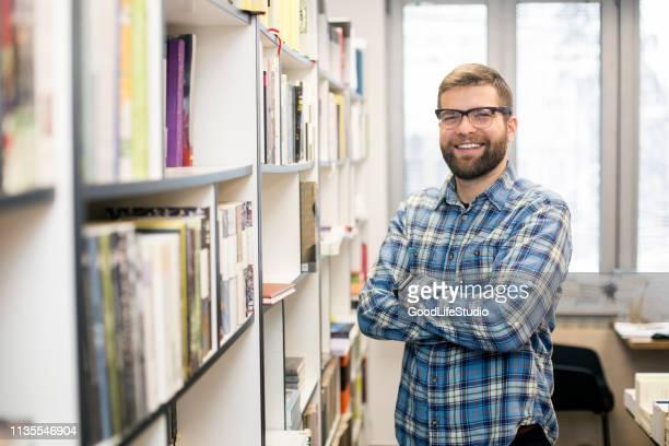 lächelnde männliche studentin - bibliothekar stock-fotos und bilder