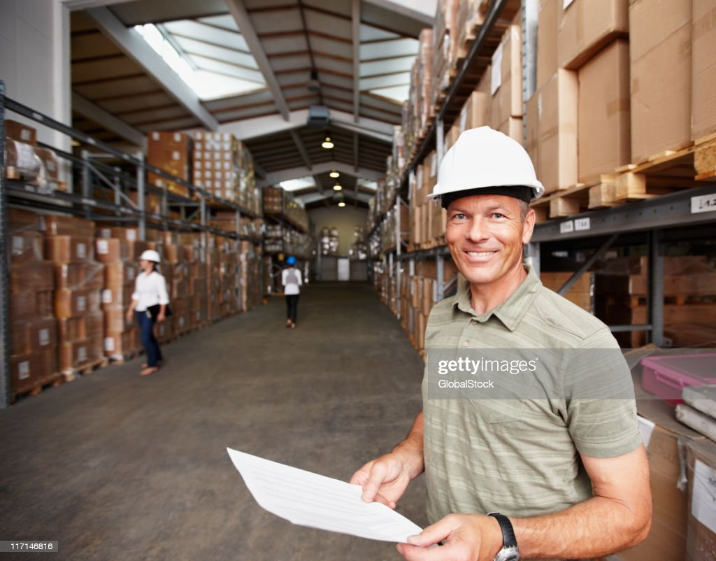 Smiling male supervisor with workers at the warehouse : Bildbanksbilder