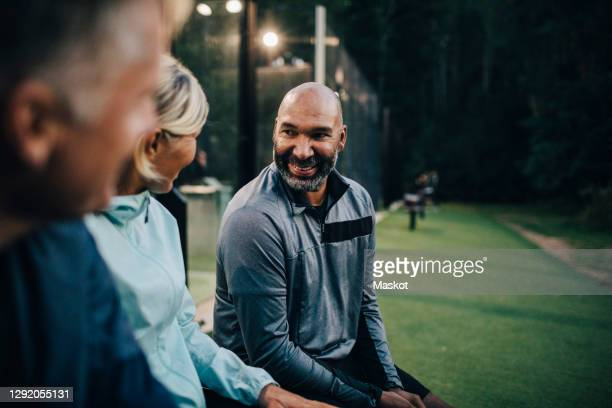 smiling male talking to friends while sitting on bench in sports court - sporting term stock pictures, royalty-free photos & images