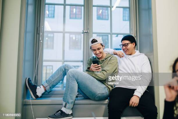 smiling male teenage students using phone while sitting on window in classroom - teenagers only stock pictures, royalty-free photos & images