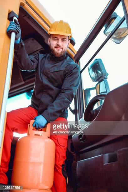 smiling male truck driver loading one more cylinder on tanker truck - butane stock pictures, royalty-free photos & images