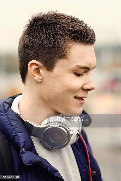 Smiling male university student with headphones around neck outdoors