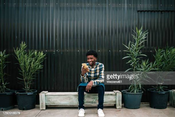 smiling male worker using mobile phone while sitting on bench against corrugated wall - 18 19 years stock pictures, royalty-free photos & images