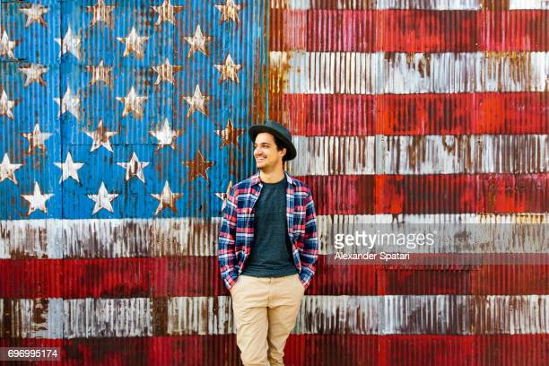 smiling man against american flag background - williamsburg new york city stock pictures, royalty-free photos & images