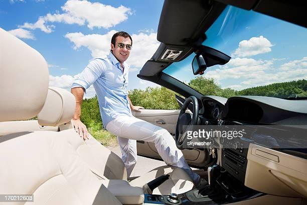 Lächeln, Mann und ein cabriolet-Auto gegen blauen Himmel.