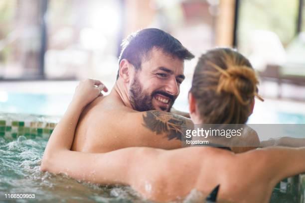 Smiling man and his girlfriend enjoying in hot tub at spa