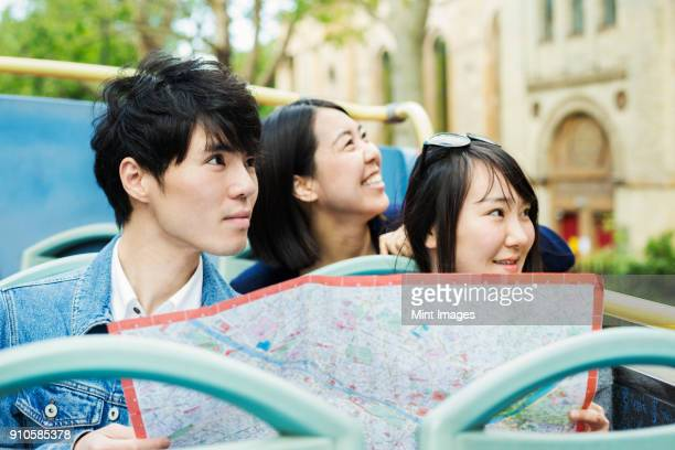 Smiling man and two women with black hair holding city map, sitting on the top of an open Double-Decker bus, driving along urban road.