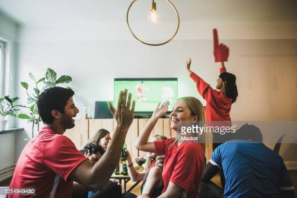 smiling man and woman high-fiving while celebrating victory with friends at home - football strip stock pictures, royalty-free photos & images