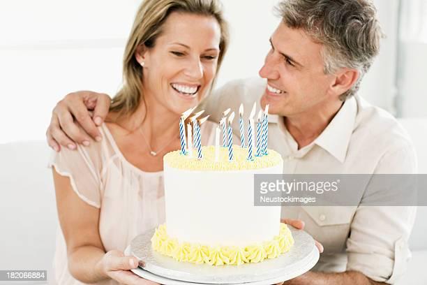 Souriant homme et femme tenant un gâteau d'anniversaire