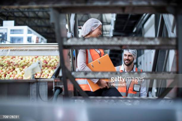 Smiling man and woman in food processing plant
