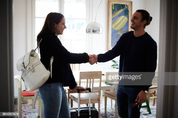 Smiling man and woman shaking hands while standing in apartment