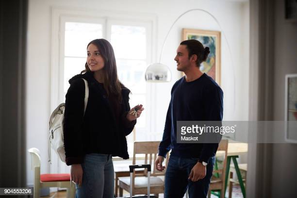Smiling man and woman standing in apartment on sunny day