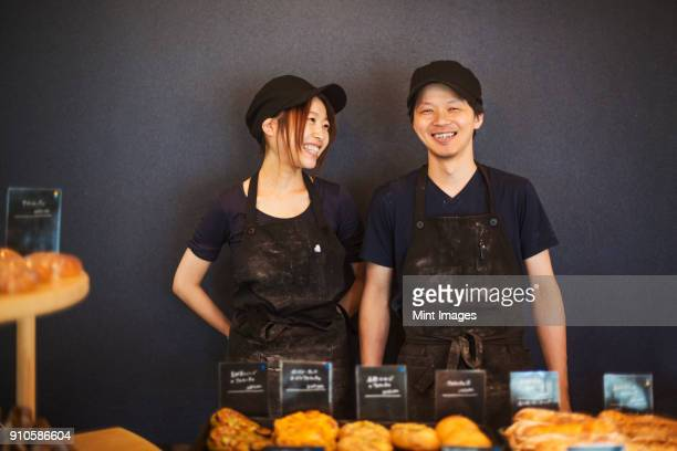 Smiling man and woman wearing baseball cap and apron standing in a bakery, trays with freshly baked goods.