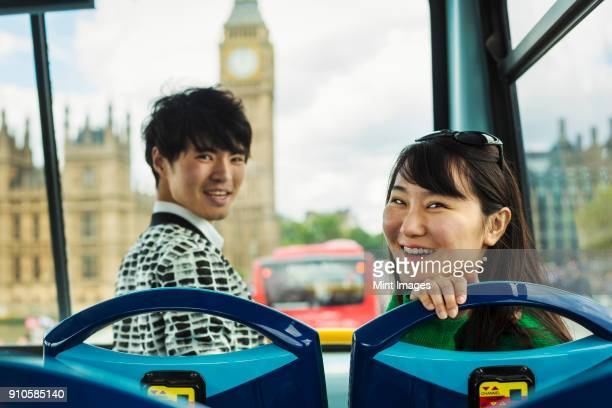 Smiling man and woman with black hair sitting at the front on the top of a Double-Decker bus in London, looking at camera, Houses of Parliament and Big Ben in the background.