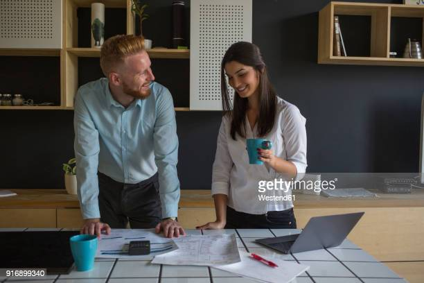 smiling man and woman with plans on table at home - fun calculator stock photos and pictures