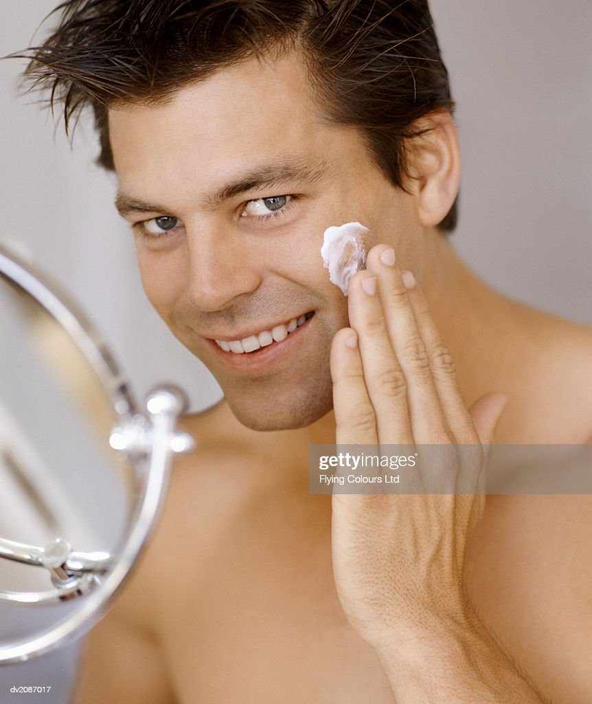 Smiling Man Applying Moisturizer to His Face : Stock Photo