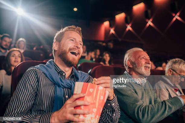 smiling man at cinema - comedy film stock photos and pictures