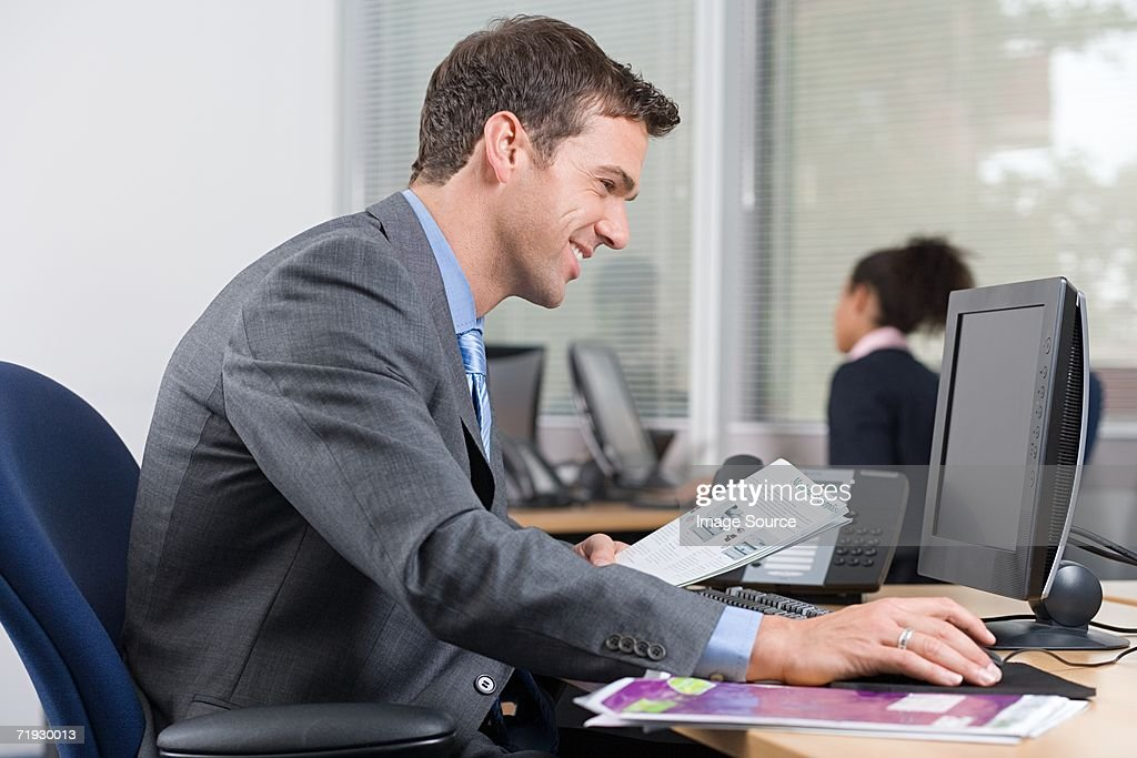 Smiling man at desk with a brochure : Stock Photo