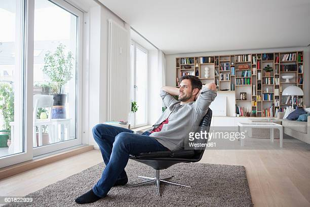 Smiling man at home sitting in armchair with hands behind head