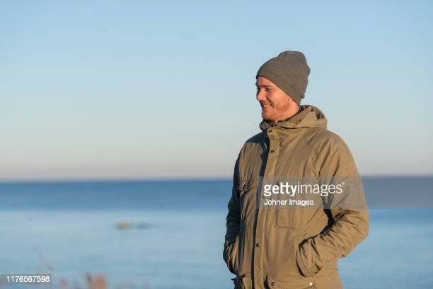 smiling man at sea - knit hat stock pictures, royalty-free photos & images