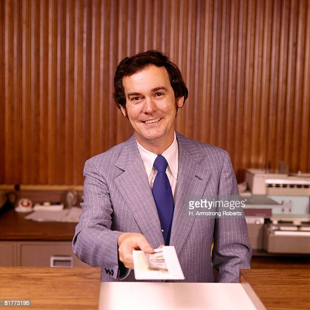 Smiling Man Bank Teller Handing Money Receipt Over Counter Banks Tellers Financial Customer Service.