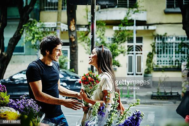 Smiling man buying flowers for girlfriend