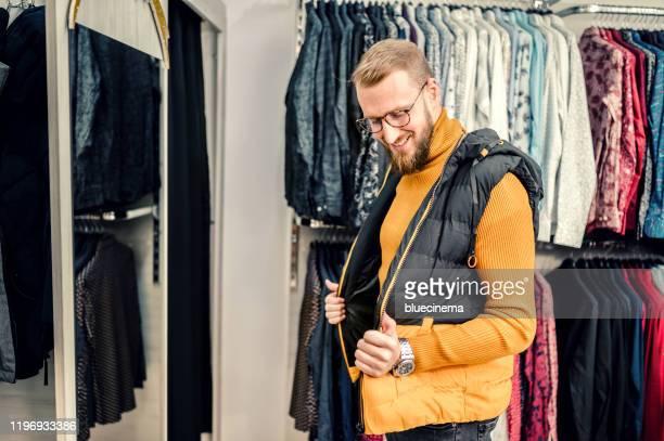 lächelnder mann kauft kleidung im kaufhaus. - westen stock-fotos und bilder