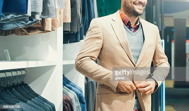 Smiling man buying some clothes at department store.
