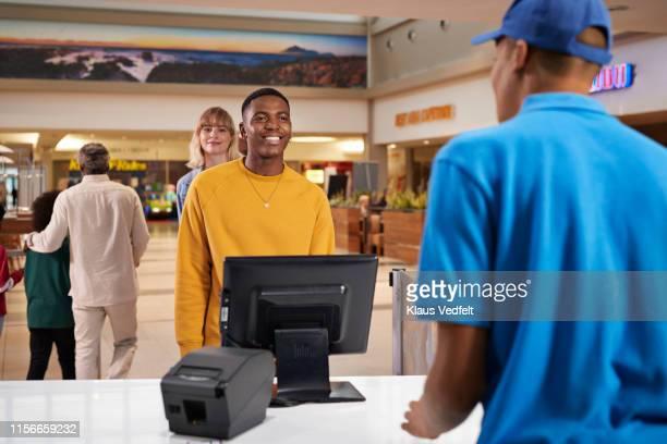 smiling man buying tickets at movie theater - schnellimbiss stock-fotos und bilder