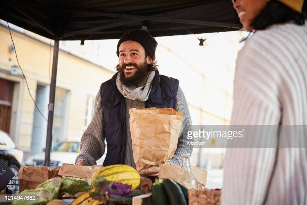 smiling man buying vegetables from female vendor at market stall - ファーマーズマーケット ストックフォトと画像