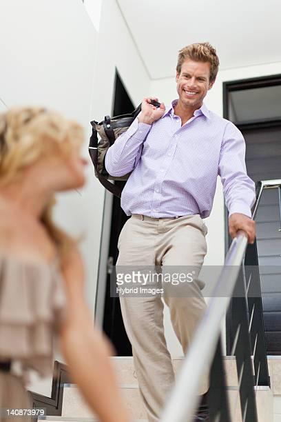 Homme souriant porter le sac en bas des escaliers