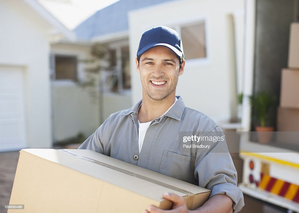 Smiling man carrying box from moving van : Stock Photo