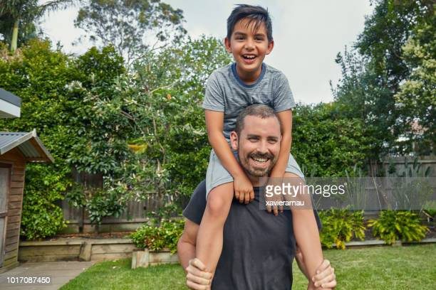 smiling man carrying boy on shoulders at yard - mixed race person stock pictures, royalty-free photos & images